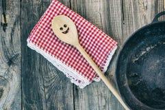 Черная сковорода чугуна с деревянным шпателем для шевелить Стоковые Изображения