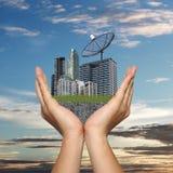 Черная спутниковая антенна-тарелка в руке бизнесмена и имеет небоскреб Стоковые Изображения