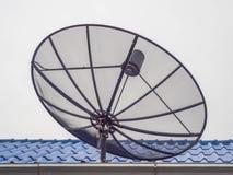 Черная спутниковая антенна-тарелка на голубой крыше Стоковое Изображение RF