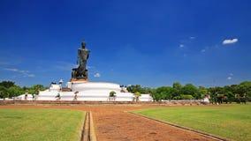 Черная статуя Будды с садом против голубого неба Стоковые Фото