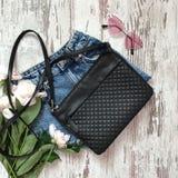 Черная сумка с шортами на деревянной предпосылке стоковая фотография