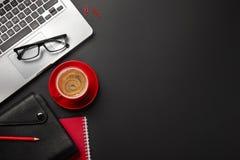 Черная таблица стола офиса с ноутбуком пустого экрана, тетрадью, чашкой кофе и другим офисом стоковая фотография rf