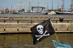 Черная форма летания флага пирата верхняя часть рангоута на шлюпке Стоковое Изображение
