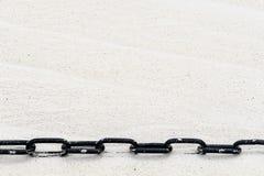 Черная цепь в песке стоковое изображение