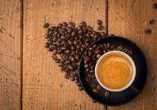 Черная чашка кофе на деревенской таблице с кофейными зернами вокруг К Стоковое Фото