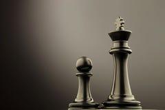 Черная шахматная фигура короля около пешки Стоковое Изображение RF