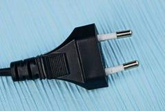 Черная электрическая штепсельная вилка черного цвета на голубой таблице Стоковые Фото