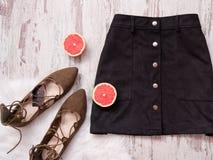 Черная юбка замши, коричневые ботинки замши, отрезанные половины грейпфрута Деревянная предпосылка женщина состава способа сторон Стоковое Фото