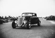 Черное & белое фото старого винтажного автомобиля припаркованного в середине дороги скоростного шоссе стоковая фотография