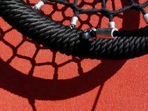 Черное качание веревочки винила в спортивной площадке с красной резиновой циновкой Стоковая Фотография