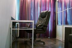 Черное кожаное кресло с таблицей владение домашнего ключа принципиальной схемы дела золотистое достигая небо к Стоковые Фото