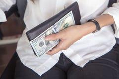 Черное кожаное портмоне с 100 банкнотами доллара в молодой женщине Стоковые Изображения RF