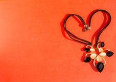 Черное ожерелье на красном цвете Стоковые Изображения
