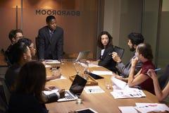 Черное положение бизнесмена для того чтобы адресовать коллег на встрече Стоковые Изображения