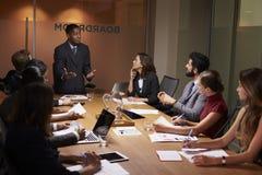 Черное положение бизнесмена для того чтобы адресовать коллег на встрече Стоковые Изображения RF