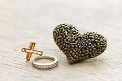 Черное серебряное сердце на деревянной предпосылке с старым христианским крестом Стоковая Фотография RF