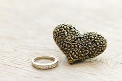 Черное серебряное сердце на деревянной предпосылке с старым христианским крестом Стоковые Изображения