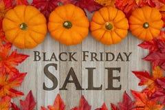 Черное сообщение продаж пятницы с листьями стоковые изображения