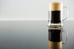 Черное стекло пива на таблице Стоковые Изображения