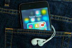 Черное iPhone Яблока со значками социального применения средств массовой информации на экране с предпосылкой джинсов джинсовой тк стоковое изображение rf