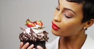 Чернокожая женщина восхищая причудливое пирожное десерта Стоковые Изображения RF