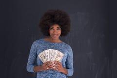 Чернокожая женщина держа деньги на серой предпосылке Стоковая Фотография