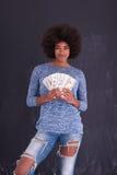 Чернокожая женщина держа деньги на серой предпосылке Стоковое Изображение