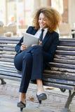 Чернокожая женщина используя планшет в городке Стоковая Фотография
