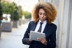 Чернокожая женщина используя планшет в городке Стоковая Фотография RF