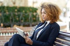 Чернокожая женщина используя планшет в городке Стоковые Фотографии RF