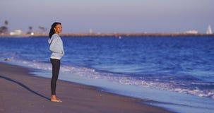 Чернокожая женщина наслаждаясь видом на океан до волн не будет приходить Стоковое Фото