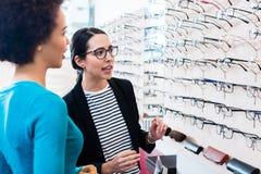 Чернокожая женщина проверяя стекла в полке optician стоковое изображение rf