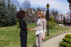 Чернокожая женщина тряся руки с блондинкой положение коммерсантки внешнее Стоковые Фото