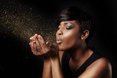 Чернокожая женщина дуя золотая пыль стоковая фотография rf