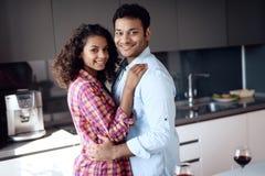 Чернокожие человеки и женщины в кухне дома прижимаются Они смотрят один другого с нежностью и любят Стоковое Фото