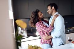 Чернокожие человеки и женщины в кухне дома прижимаются Они смотрят один другого с нежностью и любят Стоковая Фотография