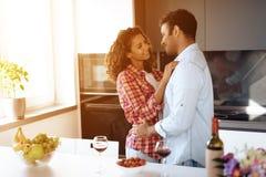 Чернокожие человеки и женщины в кухне дома прижимаются Они смотрят один другого с нежностью и любят Стоковая Фотография RF