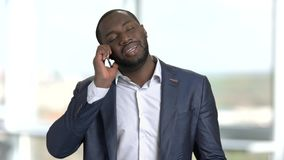 Чернокожий человек в костюме споря с кто-то на телефоне сток-видео