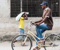 Чернокожий человек ехать его велосипед на Занзибаре, Танзании Стоковая Фотография RF