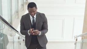 Чернокожий человек использует его телефон для дела движение медленное Афро-американский профессионал дела работает на его черни видеоматериал