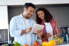 Чернокожий человек и женщина в кухне дома Они подготавливают завтрак, человек смотрят что-то на его таблетке Стоковое Фото