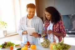 Чернокожий человек и женщина в кухне дома Они подготавливают завтрак, человек смотрят что-то на его таблетке Стоковое Изображение RF