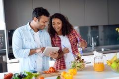 Чернокожий человек и женщина в кухне дома Они подготавливают завтрак, человек смотрят что-то на его таблетке Стоковые Фотографии RF