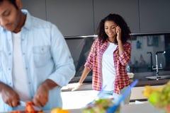 Чернокожий человек и женщина в кухне дома Они подготавливают завтрак, женщина говорят на smartphone Стоковое Изображение RF