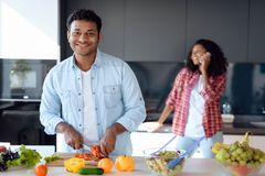 Чернокожий человек и женщина в кухне дома Они подготавливают завтрак, женщина говорят на smartphone Стоковые Фотографии RF
