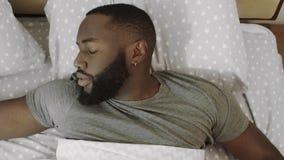 Чернокожий человек лежа в кровати Сердитый парень просыпая вверх на спальне видеоматериал