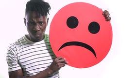 Чернокожий человек поднимает красный smiley и сердится акции видеоматериалы