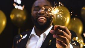 Чернокожий человек показывая свет Бенгалии к камере под падая confetti, партией Нового Года видеоматериал