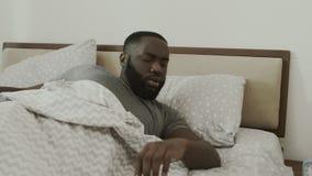Чернокожий человек просыпая вверх в утре внезапно Счастливое взрослое усаживание в кровати сток-видео