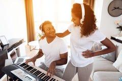 Чернокожий человек сидит в живущей комнате его квартиры и играет синтезатор Близрасположенный его девушка и он слушают как он игр стоковые изображения